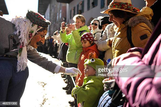Costumed participant wearing a traditional wooden mask plays with a child in the annual carnival parade on February 12 2015 in Mittenwald Germany The...