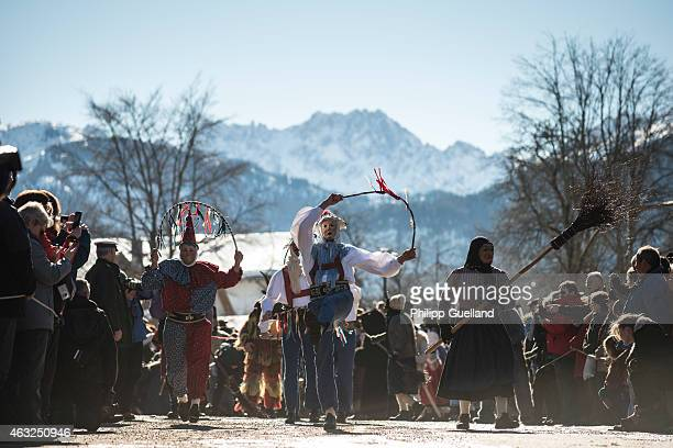 Costumed participants tossing a so called 'Jackel' perform in the annual carnival parade on February 12 2015 in Mittenwald Germany The German Alpine...