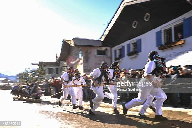 Costumed participants wearing traditional wooden masks drag a treetrunk in the annual carnival parade on February 12 2015 in Mittenwald Germany In...