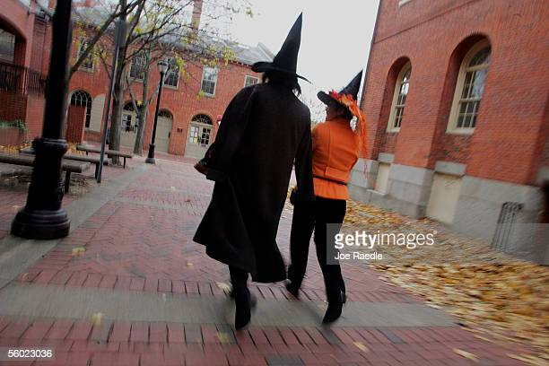 Costumed people dressed as witches walk though the street next to the old Town Hall as they visit the town where back in 1692 witch trials took place...