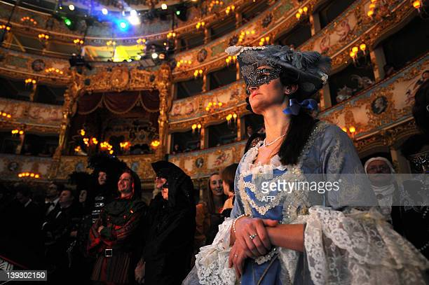 Costumed people watch performers during the 'Cavalchina' the historic Venetian Carnival ball in the famous Fenice theatre in Venice on February 18...