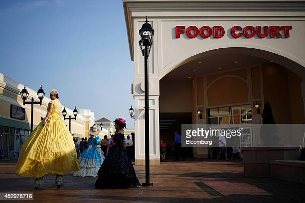 55b79185be8740 Costumed performers wait to entertain customers outside the food court at  the Outlet Shoppes of The