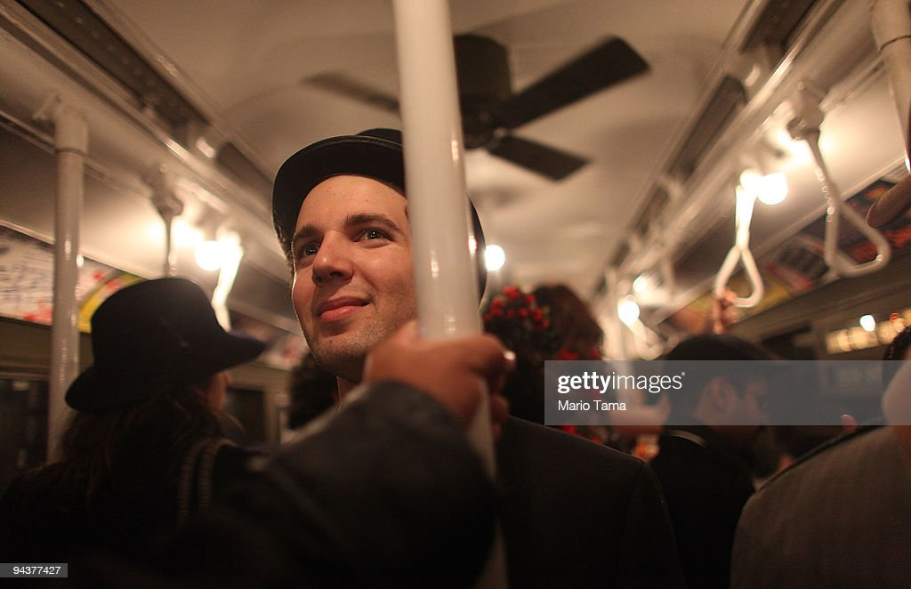 Costumed reveler Charlie Niesenbaum rides an antique subway train during a 'Vintage Tea Party' hosted by Levy's Unique New York tour group December 13, 2009 in New York City. New York City Transit is running a special subway train with cars in service from the 1930's-1970's every Sunday this month from Manhattan to Queens complete with ceiling fans and wicker seats.