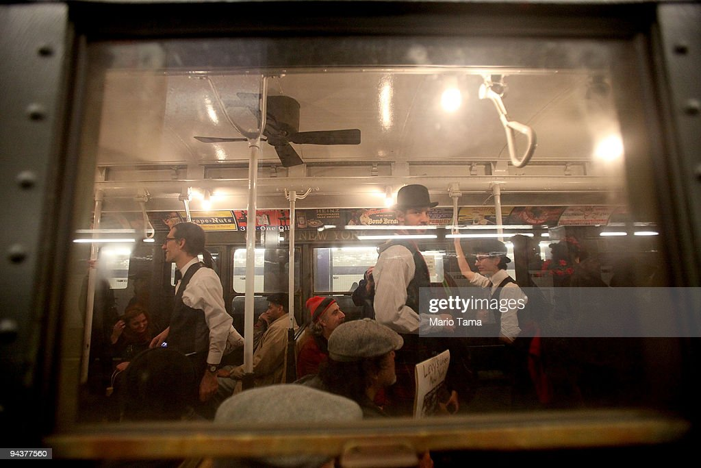 Costumed revelers ride an antique subway train during a 'Vintage Tea Party' hosted by Levy's Unique New York tour group December 13, 2009 in New York City. New York City Transit is running a special subway train with cars in service from the 1930's-1970's every Sunday this month from Manhattan to Queens complete with ceiling fans and wicker seats.