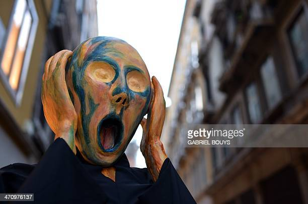 A costumed reveller wearing a mask depicting Munch's famous painting The Scream poses near St Mark's square during the carnival on February 21 2014...