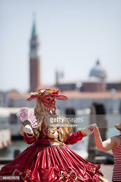 Costumed reveller woman posing near St Mark's square during the annual carnival show. The 2013 edition of the Venice carnival is untitled 'Live in...