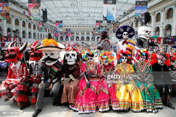 Costumed revellers pose ahead of a parade marking the national Mexican holiday 'The Day of the Dead' in the Mexican fan house in Moscow on June 29...
