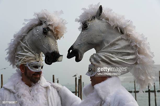 TOPSHOT Costumed revellers pose in St Mark's square after the officially launch of the Venice Carnival on January 31 2016 in Venice The 2016 edition...