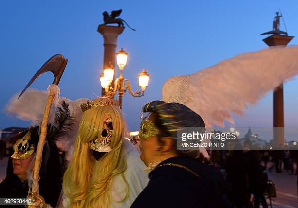 Costumed revellers walk on St Mark's square during the carnival on February 7, 2015 in Venice. The 2015 edition of the Venice carnival is untitled...