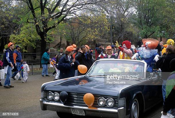 A costumed Ronald McDonald rides an open convertible through the Lincoln Park Zoo during a Halloween event Chicago Illinois 1980s Children in costume...