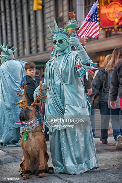 CONTENT] Costumed Statue of Liberty Busker with his dog a mastiff dog has on reindeer antlers young boy is looking back to see taken in Times Square...