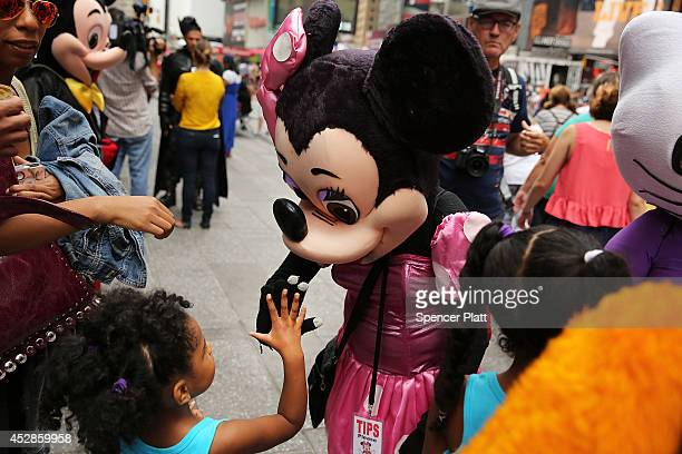 Costumed street performers stand with children while waiting for tips in Times Square on July 28 2014 in New York City In the latest incident...