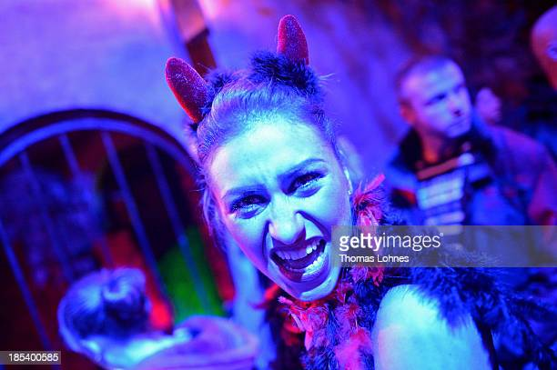 A costumed visitor poses at Frankenstein castle on October 19 2013 in Darmstadt Germany Grotesque monsters howling werewolves longnosed witches and...