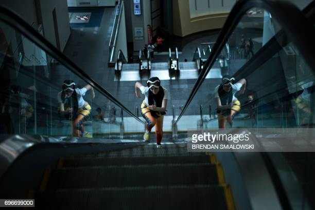 A costumed woman runs up an escalator during Awesome Con at the Washington Convention Center June 16 2017 in Washington DC / AFP PHOTO / Brendan...