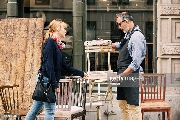 Costumer and owner discussing over chair outside shop