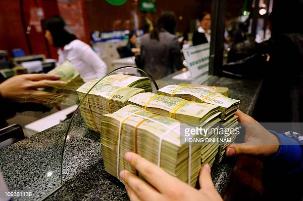 Costumer deposes bricks of dong bank notes to a local commercial bank in Hanoi on February 23, 2011. Vietnam's central bank raised its reverse...