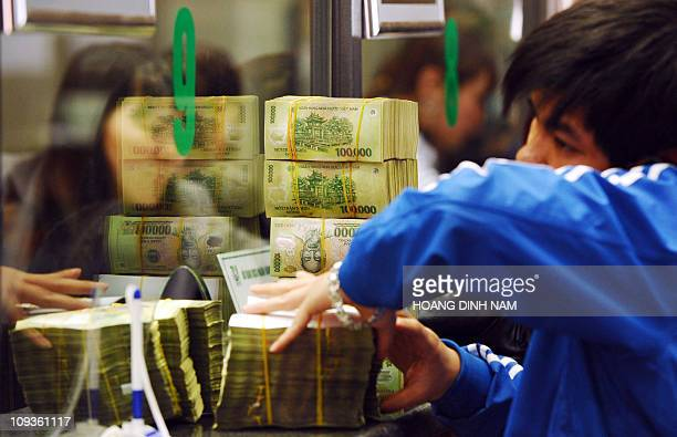 Costumer deposits bricks of dong bank notes to a local commercial bank in Hanoi on February 23, 2011. Vietnam's central bank raised its reverse...
