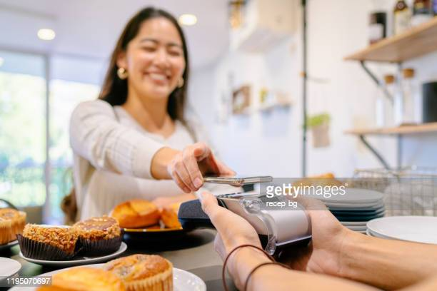 costumer making contactless payment in cafe - contactless payment stock pictures, royalty-free photos & images