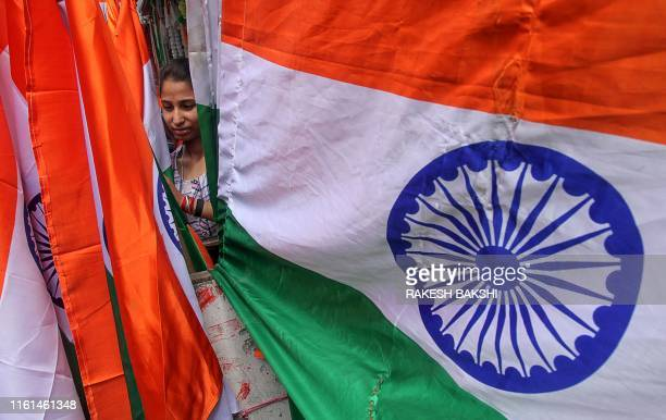 A costumer shops for Indian national flags ahead of Independence Day celebrations in Jammu on August 13 as the country prepares to celebrate its 73rd...