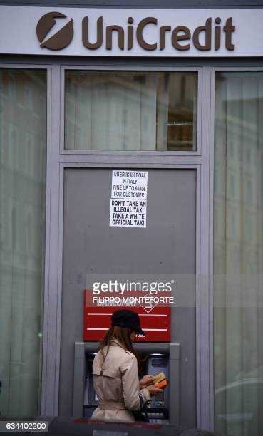 A costumer uses the automated teller machine outside a branch of the Unicredit bank in downtown Rome on February 09 2017 UniCredit SpA is an Italian...