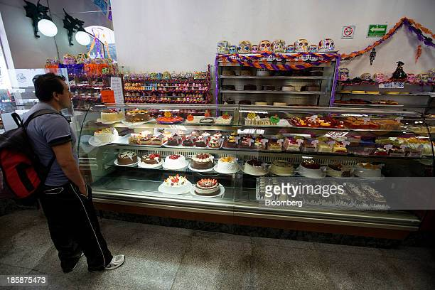A costumer views cakes at La Ideal bakery in Mexico City Mexico on Thursday Oct 24 2013 The pan de muerto or bread of the dead is a sweet soft bread...