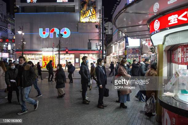 Costumers wait in line at a lottery ticket shop in Shinbashi district of Minato in Tokyo.