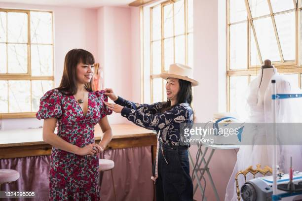 costumiers evaluating sleeve shape on dress in workshop - dress stock pictures, royalty-free photos & images