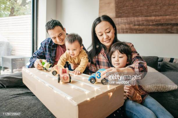 cosy family evening with kids and parents - mixed race person stock pictures, royalty-free photos & images