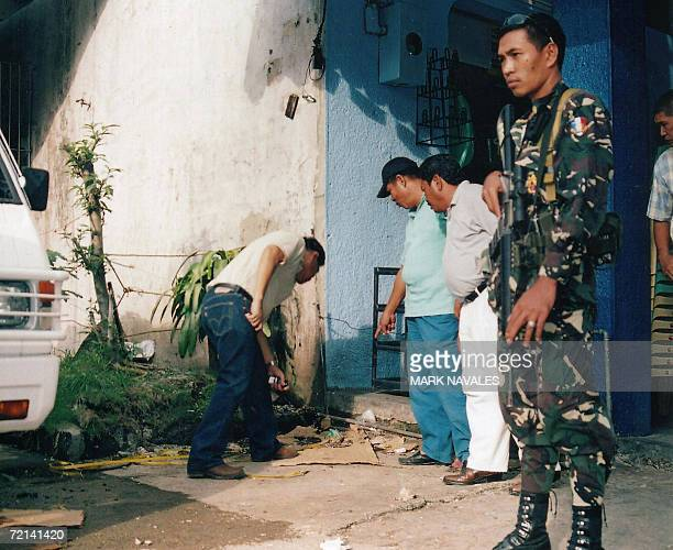 Cotabato City Mayor Muslimin Sema inspects the bomb blast scene outside a commercial building while an army soldier secure the area in this city...
