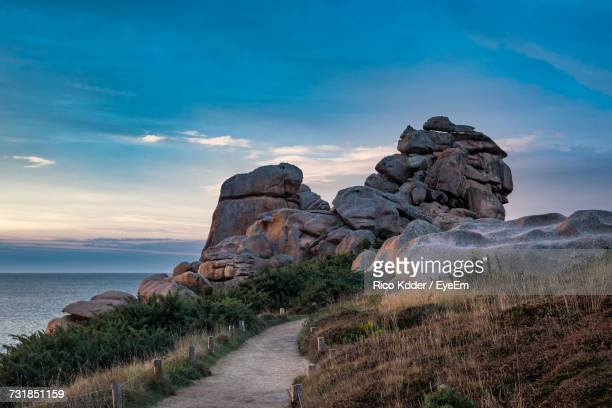 cote de granit rose against cloudy sky - cotes d'armor stock photos and pictures