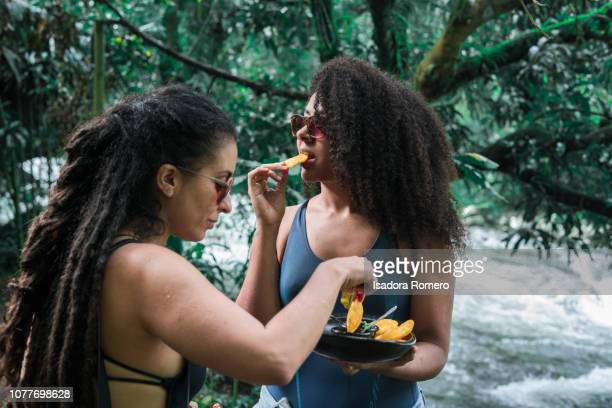 friends eating in front of the river - cali colombia stock pictures, royalty-free photos & images