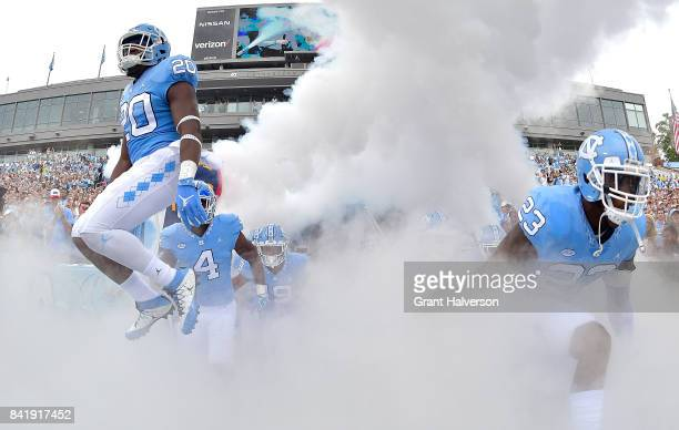 J Cotman and Cayson Collins of the North Carolina Tar Heels lead their team onto the field during their game against the California Golden Bears at...