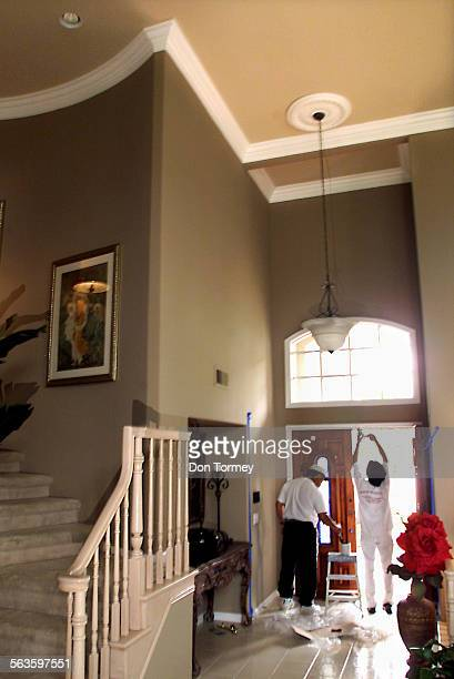 Coto de Caza––Painters patch and stain a new door at the entry to a home on Whitehollow Street in Coto de Caza The crown molding above on the ceiling...