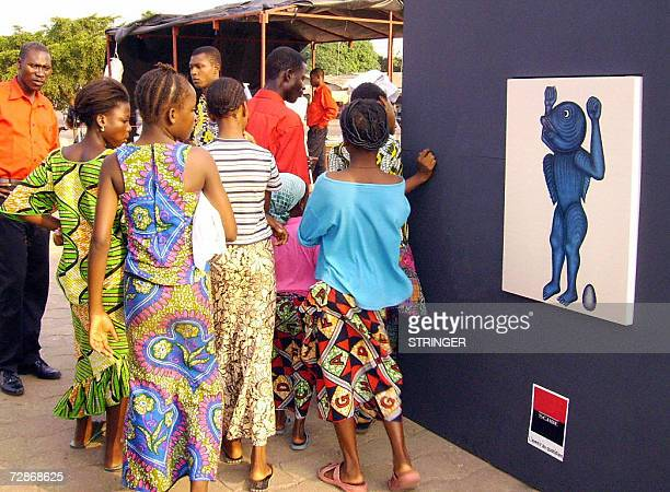 Local residents view pictures dedicated to late King Behanzin of Dahomey as part of an openair exhibition held in the capital city Cotonou 22...