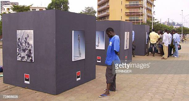 Local residents view pictures of late King Behanzin of Dahomey as part of an openair exhibition held in the capital city Cotonou 22 December 2006...