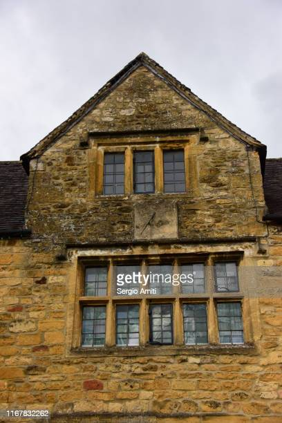 cotswolds cottage with drop shelves windows and sundial - stone house stock pictures, royalty-free photos & images