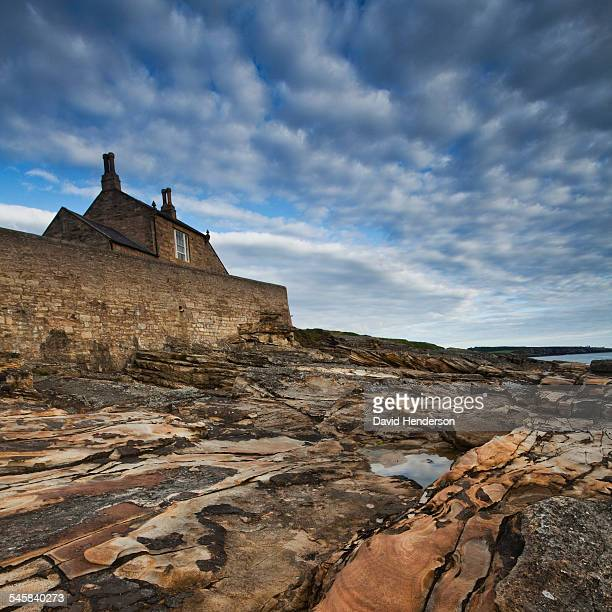cottage behind seawall - seawall stock pictures, royalty-free photos & images
