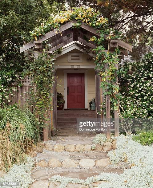 Cottage behind wooden garden arbor