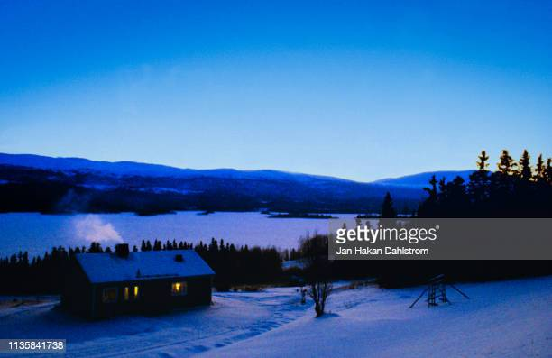 Cottage by lake during winter in northern Sweden