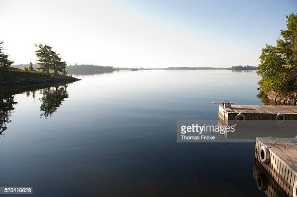 cottage dock diving board on calm lake - kenora stock pictures, royalty-free photos & images