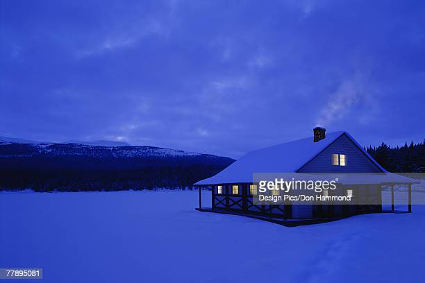 Cottage in heavy snowfall by lake