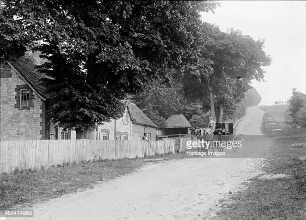 Cottage on the road leading to White Horse Hill, Uffington, Oxfordshire, c1860-c1922; with a horse drawn carriage.