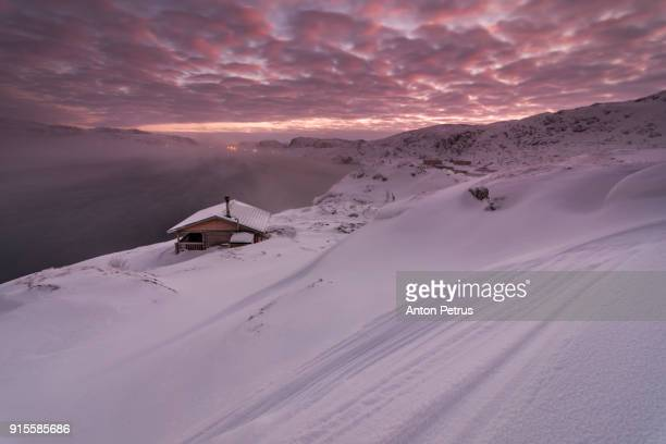 Cottage on the shore of the Arctic Ocean at dawn in winter