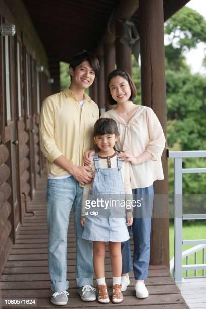 コテージの笑顔の3人家族 - 3人 ストックフォトと画像