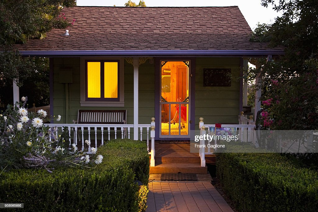 Cottage with a Woman Inside at Dusk. : Stock Photo