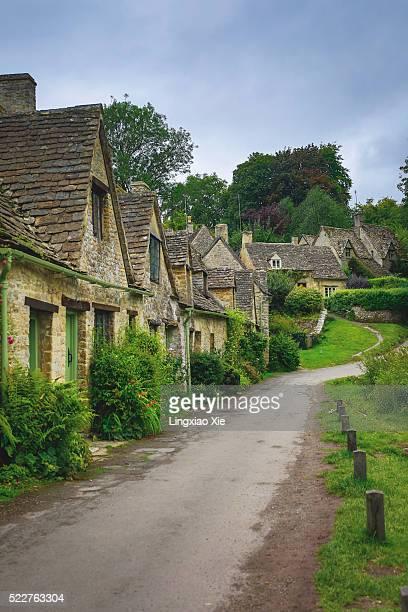 cottages of arlington row in the cotswolds village of bibury, gloucestershire, england, uk - steen bouwmateriaal stockfoto's en -beelden