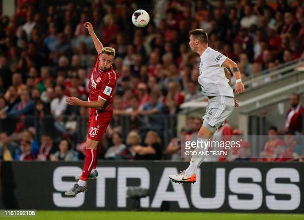 Cottbus' forward Felix Bruegmann and Bayern Munich's German defender Niklas Suele vie for the ball during the German Cup first round football match...