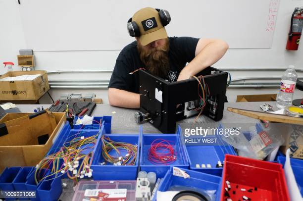 JC Cotter installs an electronic package for a Ghost Gunner milling machine at the Defense Distributed factory in Austin Texas on August 1 2018 The...