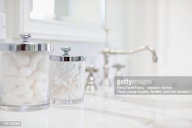 Cotton balls and swabs in containers in bathroom