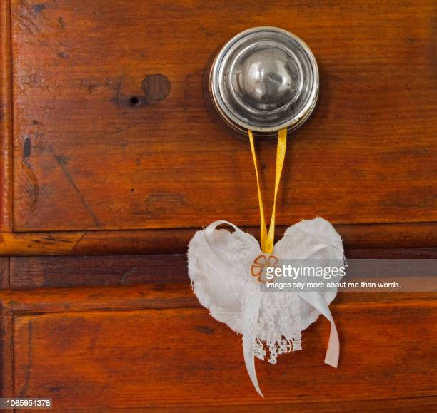 a cotton heart hanging from a drawer silver  knob. still life - レース生地 ストックフォトと画像